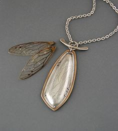 This necklace was inspired by the wings of a cicada. This is a hollow pendant, with two pieces connected with my heat-formed rivets. The top layer has been roll-printed with string to mimic the veining patterns on a cicada wing. I then use a custom cut die and hydraulic press to give the wing shape dimension. I have riveted the shape onto a sheet of sterling silver and brass bi-metal, which gives a lovely contrasting gold-tone frame around the wing, while leaving the silver exposed on the…