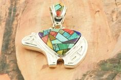 Native American Jewelry  Stunning Mosaic featuring Genuine Sleeping Beauty Turquoise, Spiny Oyster Shell, Sugilite and Blue Lapis inlaid in Sterling Silver. Bear Pendant Designed by Navajo Artist Calvin Begay. http://www.treasuresofthesouthwest.com/turquoise-jewelry.html