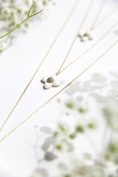 Triple layer long necklace with gold chains and ceramic white flower pendants, Felicio is a fine and elegant piece of jewelry, that will bring a subtle touch of refinement to your look