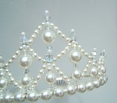 tiara was created using white glass pearls and Czech crystal AB beads all attached to a tiara band with non tarnish silver wire.     The tiara measures 2.25 inches at its highest peak.
