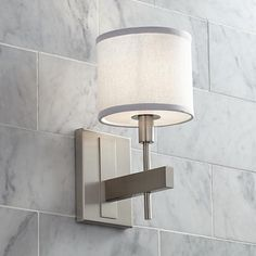 A white tone shade is paired with a satin nickel finish, giving this wall sconce fresh, chic style.