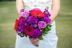 North Raleigh Florist design, with red gerberas, purple roses, purple carnations and purple stock. In love with this color combo