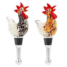 """Glass Rooster Wine Bottle Stopper Set by LS Arts. $19.50. Tops of wine stoppers are roosters, one is brown, one is orange, made of handcrafted glass. Approximately 4.5"""" tall. Stoppers have a conical shaped metal base with a silicon ruber sleeve. Each comes in a gift box. This Rooster Wine Stopper Set features a conical shaped metal base with a silicon rubber sleeve to seal in freshness. Tops are handcrafted from glass. Measures approximately 4.5"""" in height. Stoppers com..."""