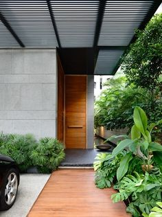 The main entrance is approached via a timber path and platform, which is cantilevered over a water garden that extends past the threshold and along the boundary wall.