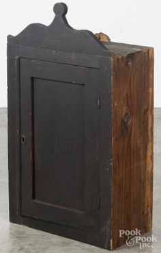 Stained pine hanging cupboard, 19th c., with a lollipop crest and paneled door, the shelved interior with a single small drawer, 31'' h., 17 1/4'' w., 9 1/2'' d
