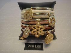 Conjunto de pulseiras redondas de metal dourado, 5 unidades com pingentes e 5 unidades revestidas com fio encerado nas cores: gelo, areia, café com leite, marrom claro e marrom escuro. Conjunto composto por  10 unidades. R$79,00