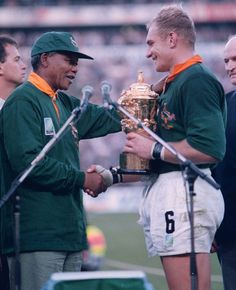 25 June 1995: President Nelson Mandela, wearing a Springboks jersey, presents the Rugby World Cup trophy to South African captain Francois P...