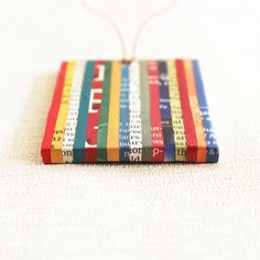 This eco friendly necklace is made entirely out of recycled materials – newspaper and cardboard. The pendant base is hand sculpted from recycled cardboard, and sanded to perfection. Thin strips of glossy newspaper, carefully chosen in vibrant shades of red, yellow, blue and green, are then neatly stuck to the sturdy base. The pendant is then given a coat of eco friendly sealant to make it sweat and splash proof. The rectangular pendant is strung through a brown waxed cotton cord. Gifts For Wife, Gifts For Her, Lesbian Gifts, First Anniversary Gifts, Recycled Jewelry, Back To School Gifts, Geek Gifts, Wooden Beads, Teacher Gifts