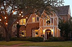 White orb lighting on the trees outside lend a magical feel - Traditional Home®