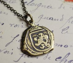 """A Song of Ice and Etsy  Brass """"cob"""" coin pendant necklace, featuring a lion rampant on one side, and a castle on the reverse. From Sue Gray Jewelery."""