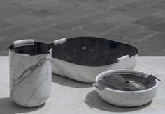 White Carrara marble kitchen containers with satin steel covers.