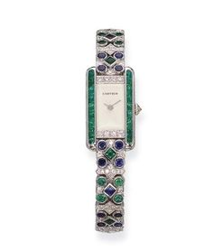 AN EMERALD, SAPPHIRE AND DIAMOND WRISTWATCH, BY CARTIER   The engine-turned dial with diamond and buff-top emerald sides to the emerald and by meghan