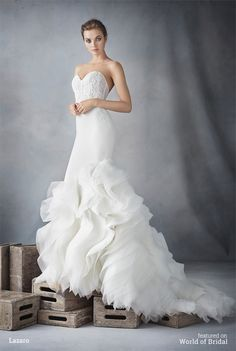 Ivory crepe trumpet bridal gown with organza textured skirt, strapless sweetheart neckline, shear corseted Chantilly lace bodice, natural waist, crepe skirt finished with layered ruffled organza, chapel train.