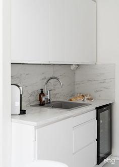 Tämän vaalean keittiön tekee mielenkiintoiseksi kaunis välitilan laatta #keittiö #keittiökaapit #keittiölaatta #työtaso