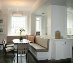 Suzie: Curated - Built-in banquette with gray vinyl cushions, white & black basketweave chairs, ...