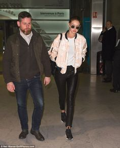 Stylish: Gigi looked cool in her peach bomber jacket as she landed with a male companion...