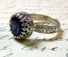 A beautiful handmade sapphire ring. Constructed completely in sterling silver. The gemstone is actually a 10mm round lab created blue sapphire. The band has a lovely floral pattern which gives it a Renaissance look. The ring has a raised bezel so that the matching band can fit