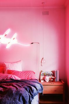 Tom Adair's neon artworks infuses the white bedroom with a vivid pink glow...