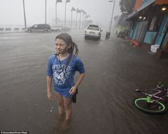Hannah Coles, 9, takes a break from riding her bicycle through the ankle-deep…