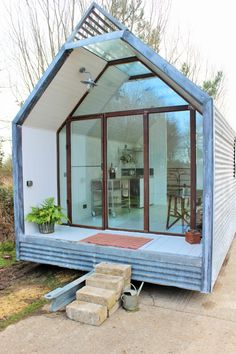 I like the glass doors that cover the entrance as they make the house appear larger. I also like the triangular shape of the roof as it enables room for a loft bed.