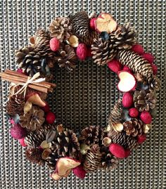 This 14 inch grapevine wreath base is covered in pinecones, nuts (both natural and colored), and dried apple slices, and is accented by a little