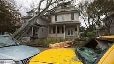 A tree leans against a house Tuesday, Oct. 30, 2012, in the Bay Ridge neighborhood in the Brooklyn borough of New York, while another tree lies on a taxi with a shattered rear. (AP Photo/David Boe)