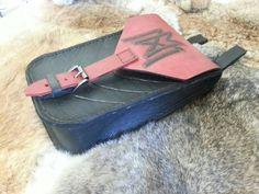 Bolsa feita em couro, com fechamento em fivela, costura e marcação a manual.