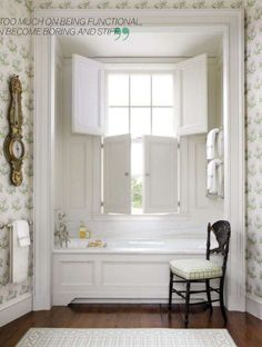 Beautiful, soft, country bathroom in a home by Gil Schafer and Miles Redd. Lightest green and blue floral wallpaper, surrounds a wonderfully inset paneled bath tub which is placed under a shuttered window. A gorgeously composed space.
