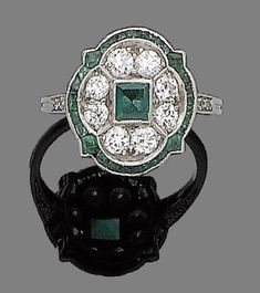 An art deco emerald and diamond brooch and ring, circa 1920 The navette-shaped openwork brooch millegrain-set throughout with old brilliant and single-cut diamonds, set to the centre with two square-cut emeralds, accompanied by a ring, centrally-set with a square-cut emerald, within an old brilliant-cut diamond and calibré-cut emerald surround, diamonds approx: brooch 1.45cts total, ring 0.40ct total, brooch length 5.4cm