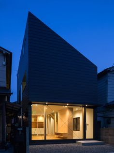 Japanese family home featuring a glass-fronted house and a steeply angled roof.