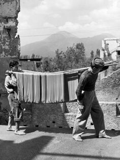 Italian Vintage Photographs ~ Alfred Eisenstaedt - Boys working in a pasta factory bringing the pasta to the drying room