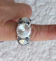 Diesen Edelstahlring lassen Kristalle (MADE WITH SWAROVSKI® ELEMENTS) die in einem Bett aus Epoxidharz liegen glitzern und strahlen.Der Ring hat die EU Größe