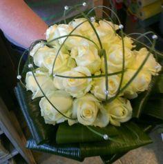 Bruidsboeket met witte avalanche rozen doorregen met steel gras net parels. ..