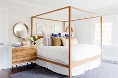 Neutral bedroom with a wooden canopy bed, a dresser and a mirror