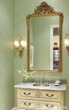 An ornate gilt-framed mirror and sconces lend sophistication to this powder room. Peaceful green walls feature a subtle weave pattern for added texture.  Tour the rest of this Louisiana home here.  Photo: Werner Straube Design: Marlene A. Shaw