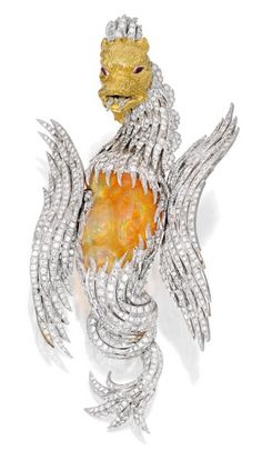 18 Karat Two-Color Gold, Fire Opal, Diamond and Ruby 'Griffin' Brooch, Buccellati: Designed as a fantastical griffin, the torso set with a Mexican fire opal weighing 42.95 carats, accented by round diamonds weighing 18.25 carats, completed by marquise-shaped ruby eyes weighing .15 carat, gross weight approximately 61 dwts, signed Buccellati; fitted with pendant loop.