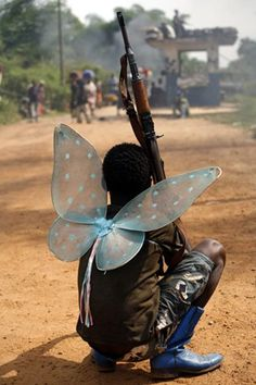 a stunning picture of the reality of child soldiers....a child wearing wings toting a gun....innocence lost...