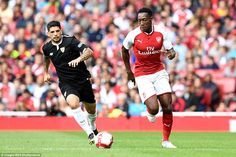 Danny Welbeck shows his impressive turn of pace as he sprints away from Sevilla midfielder Ever Banega but fails to finish
