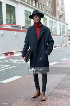 Fashion and celebrity stylist Jay Xyyx wearing an H and M hat, villain coat, Topman jeans and boots, clutch bag and glasses from a vintage boutique on day 2 of London Collections: Men on January 10, 2015 in London, England.