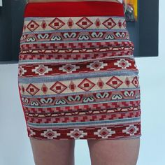Aztec print skirt NWOT Brand new no tags Front of skirt features a fabulous threaded Aztec print while the backside is solid red. Pair with a white top and heels!  Size medium  Zips up on side Material 76%polyester 20%rayon, 4%spandex Length approx 15.5 Waist side to side is approx 14.5 ( has alittle stretch) Dani Collection *price is firm unless bundle (5%off bundles of 3 or more) *No trades Skirts Mini
