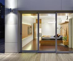 Glass doors by Tiltco separate the master bedroom from a deck. Walnut bed by Luis Dos Santos Sousa.