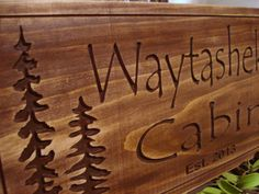 Our stained wooden carved personalized cabin sign with pine trees and pine cones is a classic rustic contemporary style. Each custom wood