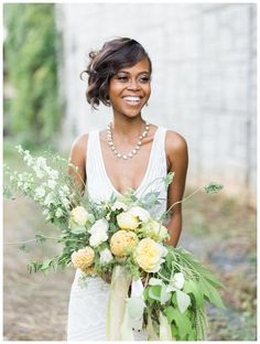 Beautiful bride with a bouquet of yellow and ivory blooms. Dress by Wtoo from The White Magnolia Bridal Collection in Atlanta, GA, accessories from Perfect Details. Bouquet by Amanda Jewel Floral + Design. Model styling by Chawncia Bythwood, hair and makeup by Scoobie West & Company. Image by Elle Golden Photography.