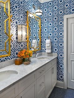 Gorgeous bathroom features walls clad in blue Moroccan wallpaper, Agadir Screen Noir Wallpaper, lined with two gold bamboo mirrors and white dual washstand topped with polished marble fitted with polished nickel faucets alongside a blue penny tile floor. Blue Penny Tile, Penny Tile Floors, Bathroom Feature Wall, White Bathroom, Home Design, Interior Design, Design Ideas, Moroccan Wallpaper, Navy Wallpaper