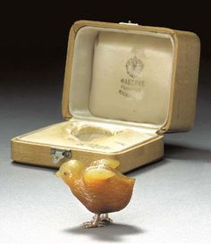 A JEWELLED GOLD-MOUNTED AGATE MODEL OF A CHICK by Fabergé, circa 1890. Realistically carved, with cabochon ruby eyes and gold feet, in original fitted case stamped, 'Fabergé, St. Petersburg, Moscow, London' with Imperial warrant