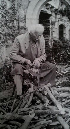 Jung cutting wood, Bollingen. ( yes he is cutting wood in his suit with an apron over it!)
