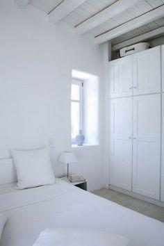 Η ξύλινη ντουλάπα αποτελεί το κύριο «έπιπλο» της κρεβατοκάμαρας.  Το γαλάζιο, κεραμικό κανάτι διακόπτει ευχάριστα τη λευκή κυριαρχία.