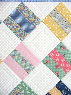 The contrast of the white-on-white background of this baby quilt with the rainbow of 30s reproduction fabrics makes me think of summer time...