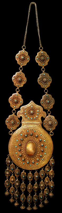 Large, rare, silver-gilt, turquoise and agate equestrian Koranic amulet case; Emirate of Bukhara; 19th century. Height: 92 cm, width: 25 cm; weight: 1.784 kg  This massive hollow ornament of gold-covered, high-grade silver embellished with semi-precious stones was made to hold Koranic verses and other items with amulet-like properties. Most were probably worn around the neck of a horse, most likely on the occasion of a wedding procession