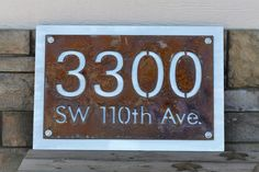 """Rustic Metal House Number and Street Name, 18x12"""" Size. Rustic house number address signs are highly visible and a beautiful addition to your front door! Sure to catch attention, you'll never have to worry about guests finding your address number again. Shiny aluminum backing plate is polished for an eye-catching reflection in any light. Makes a great house warming gift! Choose from 5 text styles as shown in final photo. House number and street name sign itself is 18"""" wide and 12"""" tall."""